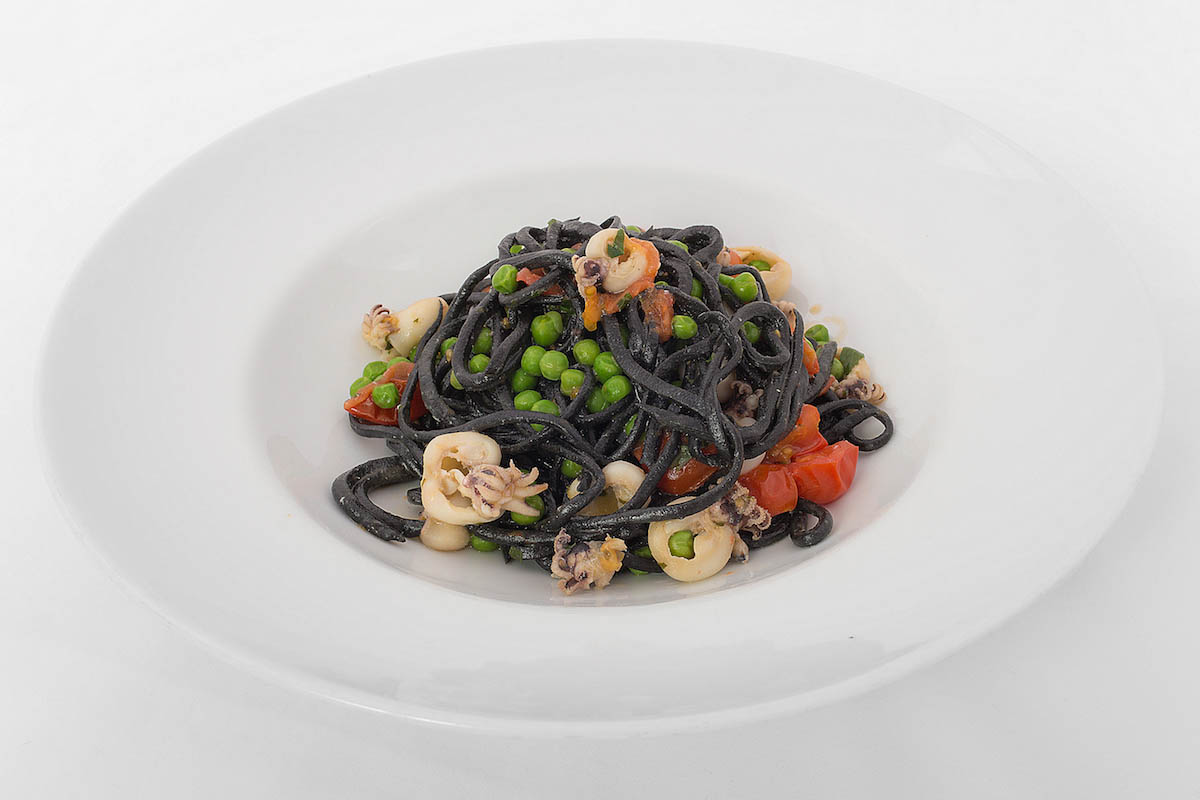 Homemade squid ink spaghetti with calamari, peas and lemon