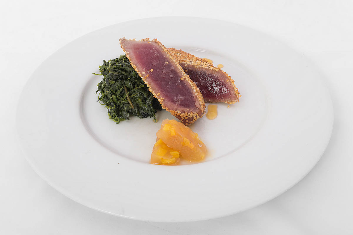 Tuna fillet in sesame crust with peach tartare and apple vinegar reduction with butter spinach