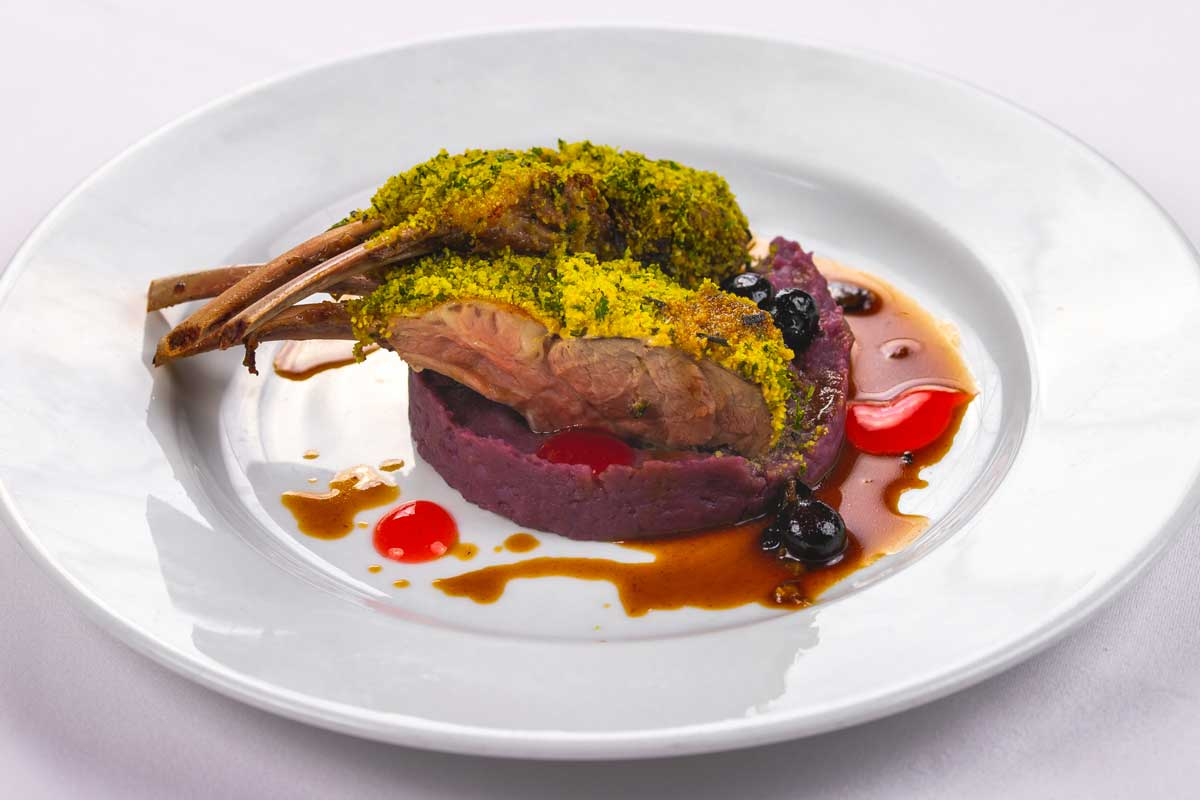 Lamb in herb crust with purple carrot cream, blueberries and orange gel